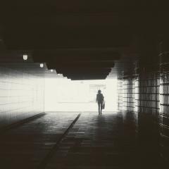 Woman walking alone through tunnel